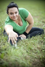 Happy overweight woman stretching in a park. Shallow DOF.